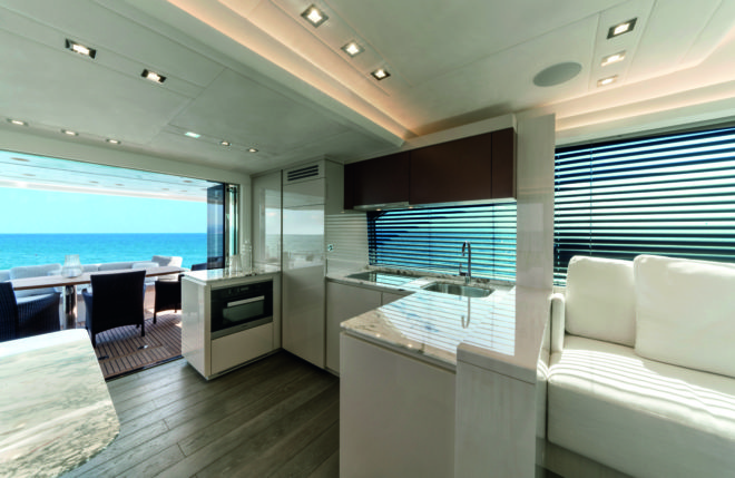 Well protected by the flybridge overhang, the cockpit has double access to the bathing platform, space for chairs around the table, and easy access to the aft galley